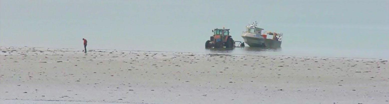 Am Strand von Pirou holt einTraktor ein Fischerboot aus dem Wasser