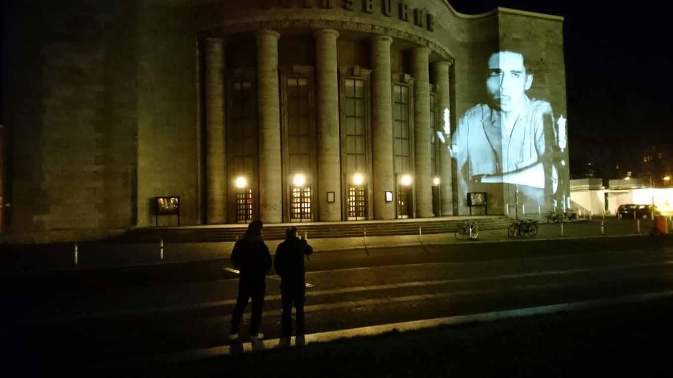 Zwei Männer betrachten eine nächtliche Projektion von Fotos