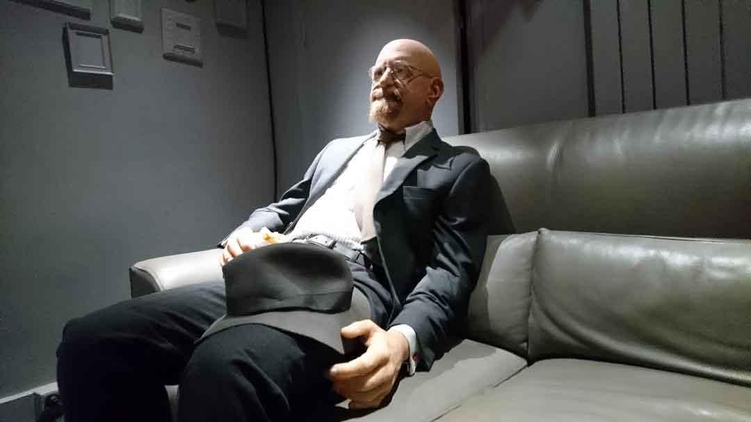 Silikonfigur (James Fallon) auf einer Couch.