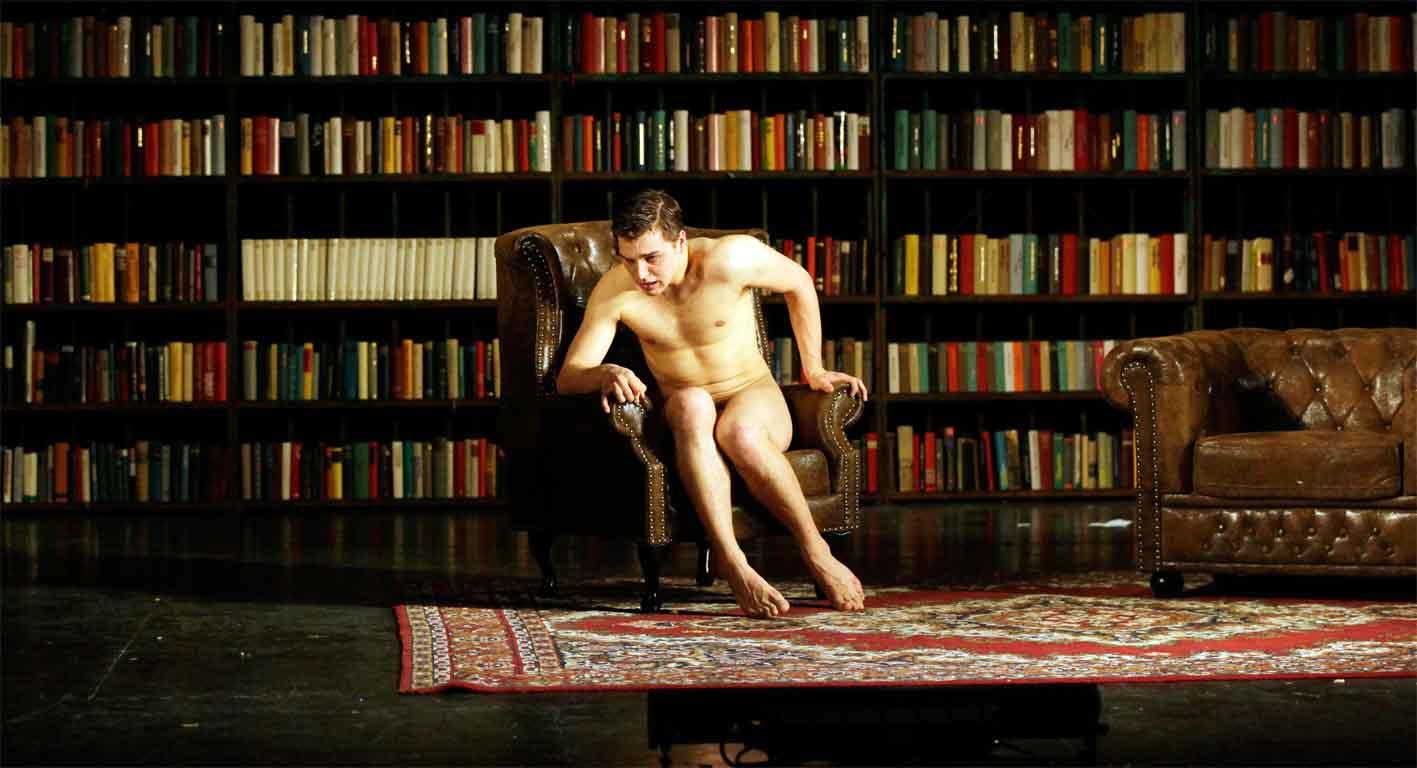 Ein nackter Affe vor der Bücherwand